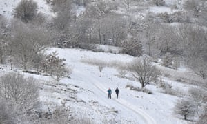 A couple walk down a snow-covered hill in Werneth Low country park near Hyde in Greater Manchester on 31 January 2019