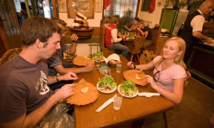 Wiener schnitzels hang over the plate edge at Restaurant Figlmueller.