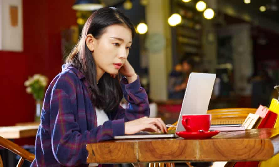 Young woman using laptop in coffee shop.