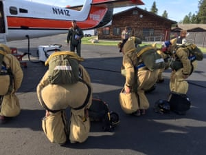 Smokejumpers do a final drill before boarding a flight for a practice jump.