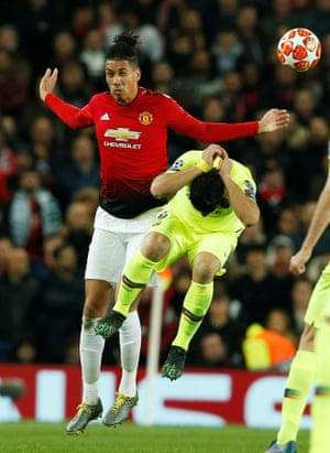 Manchester United's Chris Smalling beats Barcelona's Luis Suarez in the air.