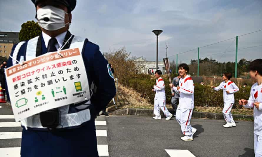 Azusa Iwashimizu carries the Olympic Torch as a guard holds a sign about Covid-19 precautions, during the torch relay.