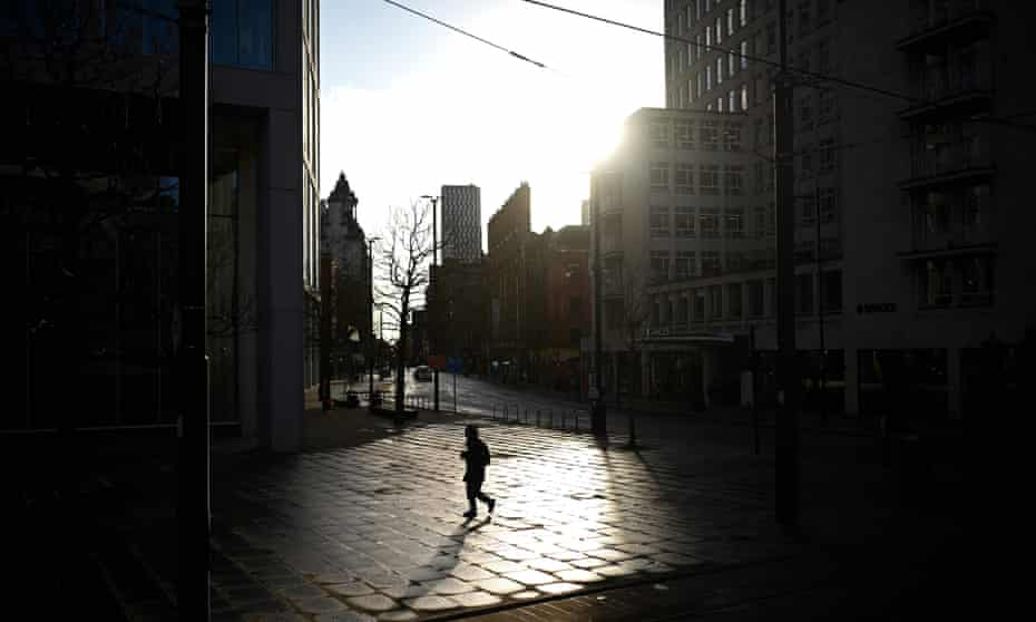 A pedestrian walks in an empty St Peter's Square in Manchester, north west England on 5 January 2021.