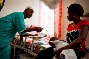 Edwin Yarkopwalo (left) takes down details about a baby in order to register its birth at the Kakata Rennie hospital in Margibi.