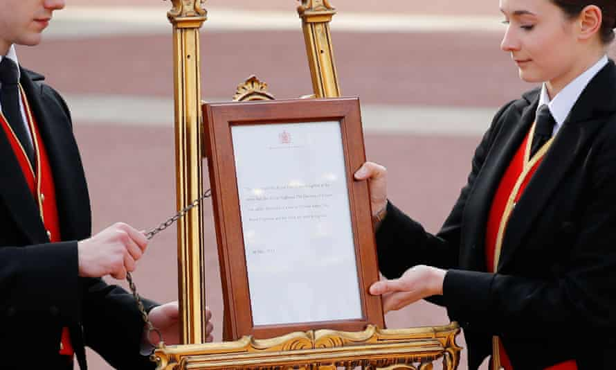 Members of staff set up an official notice on an easel at the gates of Buckingham Palace.