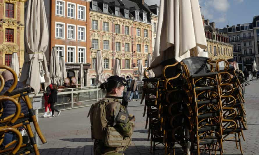A soldier walks past stacked chairs in front of a cafe in Lille, northern France