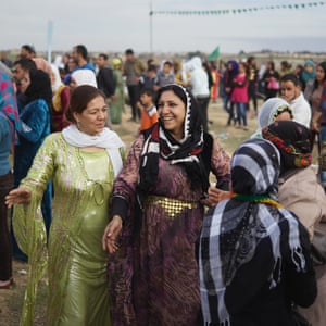 Kurdish women in cultural clothing dance during an International Women's Day celebration in Rojava.