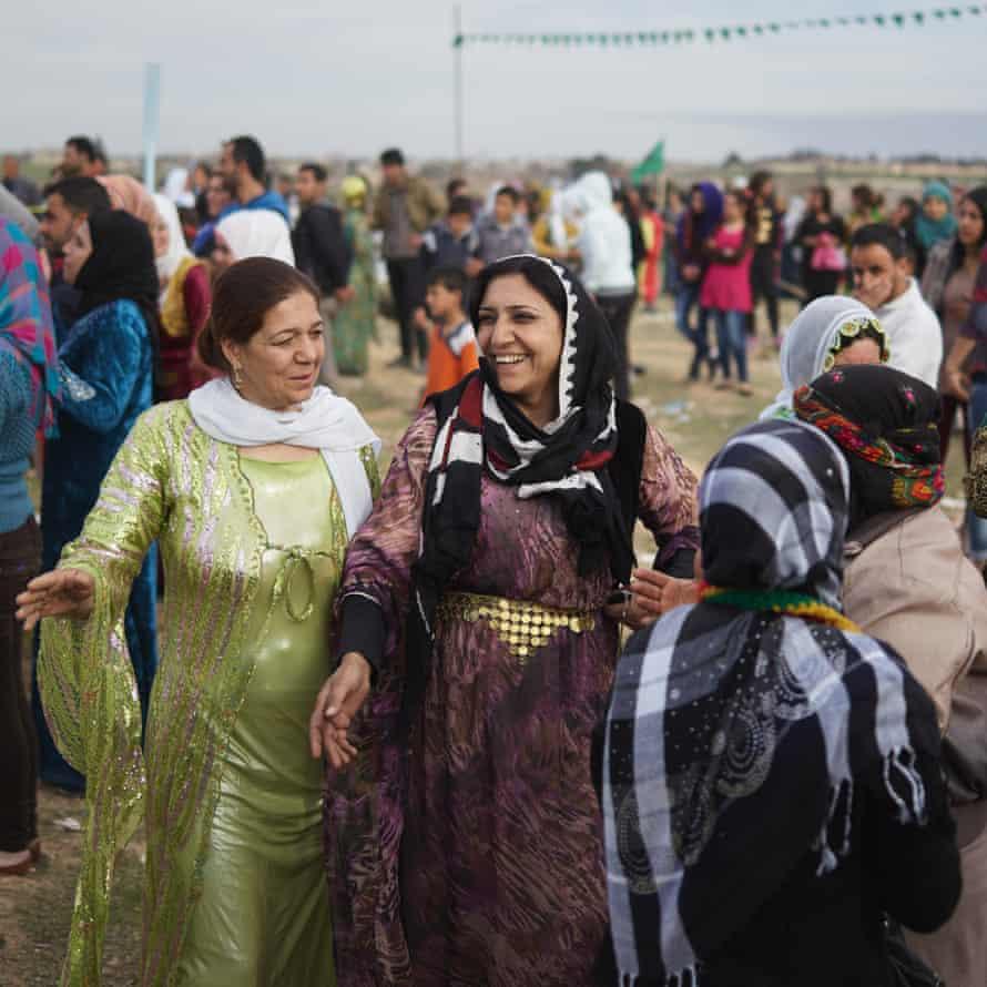 Kurdish women in cultural clothing dance during an International Women's Day celebration in Rojava.