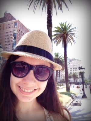 Woman with sunglasses on against palm tree background.