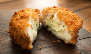 A cod fishcake, ready for eating. Although it should be on a plate, not a board.