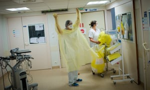 A nurse prepares to enter a room to care for a coronavirus patient at a hospital in Nantes, France