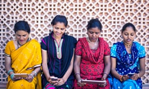 Using new technologyFour indian women using new digital devices.
