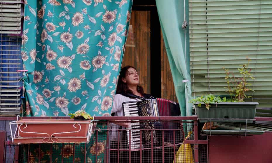 A woman plays the accordion on the balcony of her home in Milan, as part of a movement throughout Italy attempting to bring people together and lift spirits during the coronavirus lockdown.