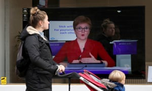 A woman with a pushchair walks past an image of Nicola Sturgeon on a TV screen
