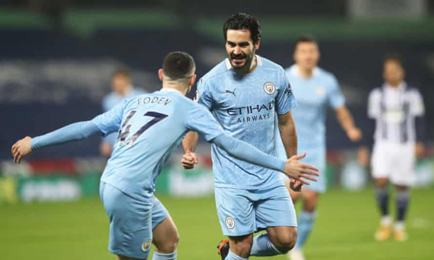 Manchester City's Ilkay Gundogan celebrates scoring his first goal against West Brom with teammate Phil Foden.
