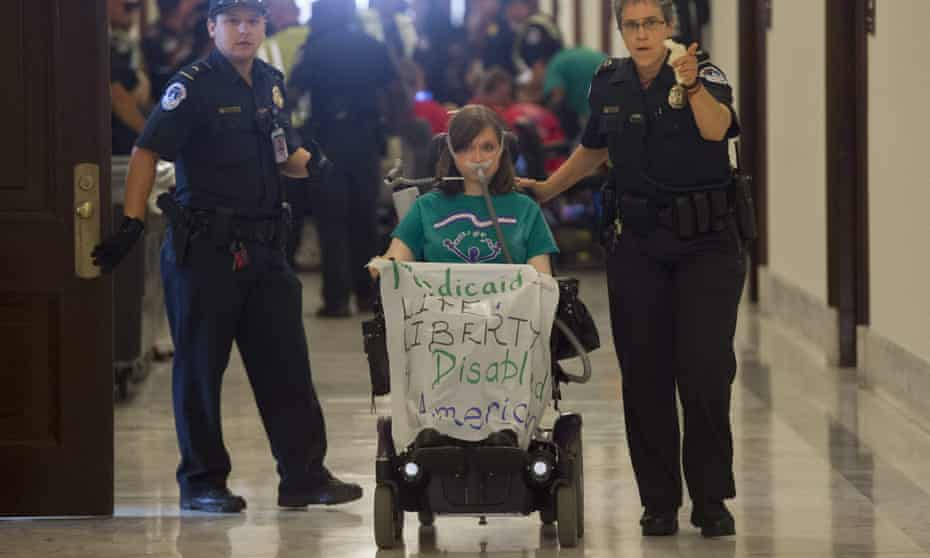 Disability advocates hold a protest outside the office of Senate majority leader Mitch McConnell on 22 June. Senate Republicans have released their draft healthcare bill.