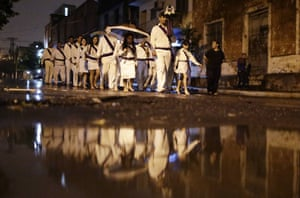 Catholics walk barefoot in the rain singing religious songs during their procession through the city