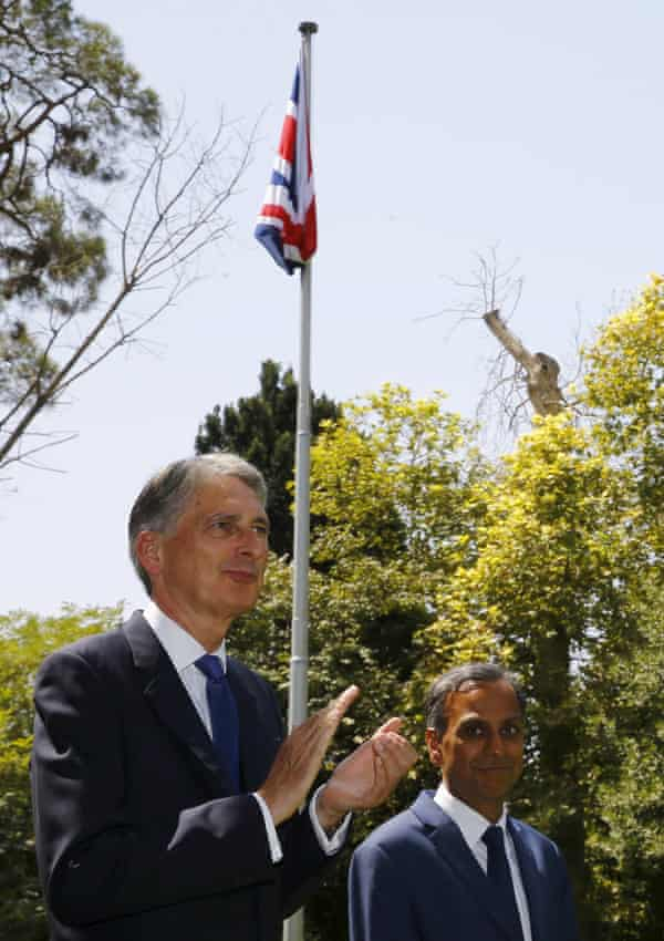 Hammond applauds as the union flag is raised at the embassy.