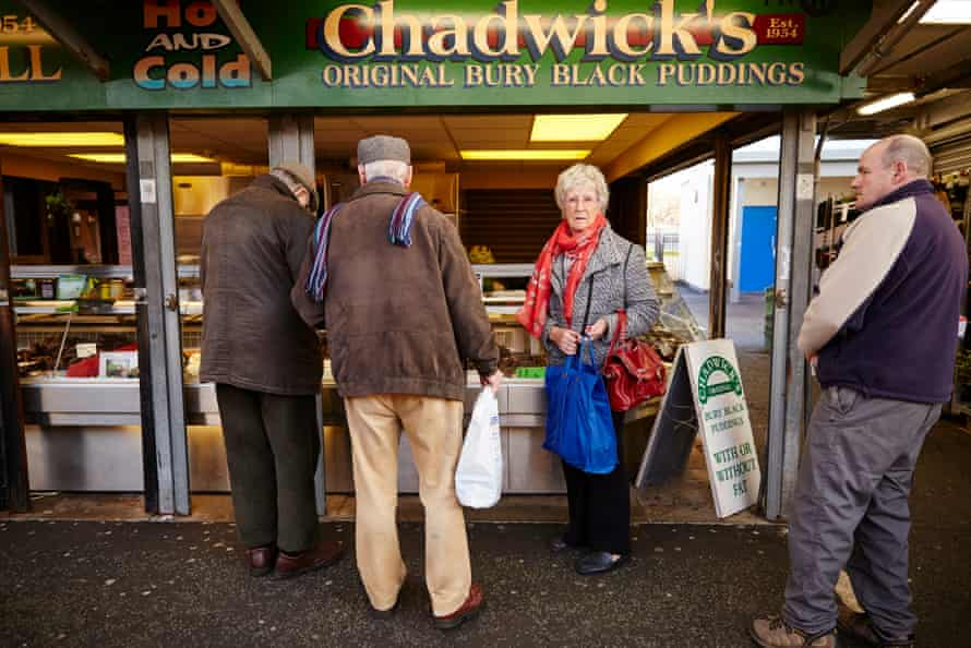 Customers line up for black puddings from the Chadwick's stall on Bury market