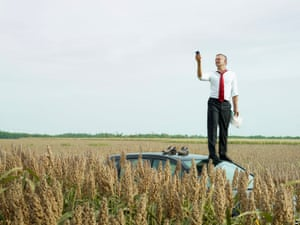 Man on top of his car in a field looking at his GPS