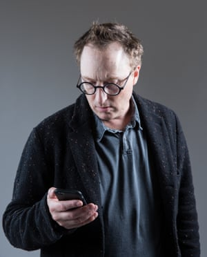 Jon Ronson looking at his mobile phone