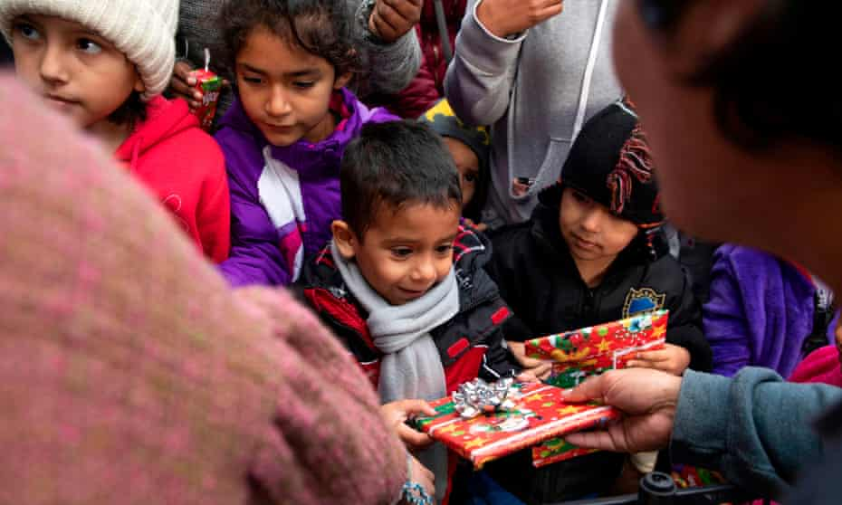 Migrant children receive Christmas gifts from as they wait for visas from US migration authorities outside El Chaparral port of entry in Tijuana.