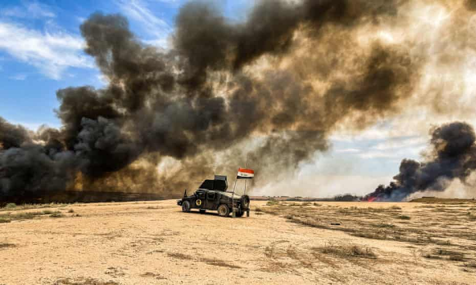Iraqi forces burn reed and grass to clear marshes and irrigation canals during the search operation.