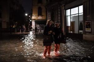 People wearing waterproof clothing cross a flooded street