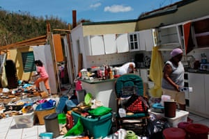 Family members collect belongings after hurricane force winds destroyed their house in Toa Baja, west of San Juan