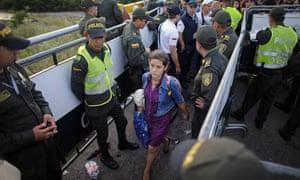 Police stand guard as a Venezuelan woman crosses into Colombia through a bridge linking San Antonio del Tachira, Venezuela, with Cucuta, Colombia.