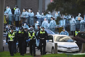 Police officers and healthcare workers in protective clothing outside a North Melbourne public housing tower during a major Covid outbreak in the city.