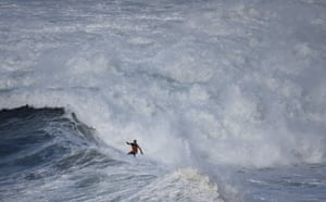 A surfer drops in on a large wave at Praia do Norte in Nazaré, Portugal.