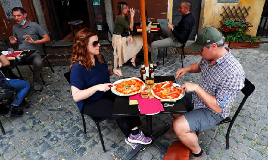 People eating pizza outside a restaurant in Rome