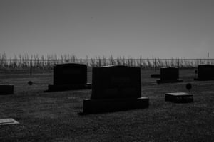 A dead corn field lies behind the fence of a local cemetery in Atkins, Iowa.