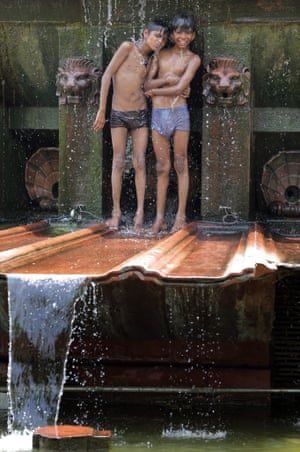 Children cool off at a fountain in Delhi