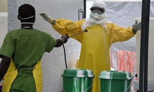 A health worker is decontaminated at an Ebola treatment centre run by the humanitarian organisation Doctors Without Borders.