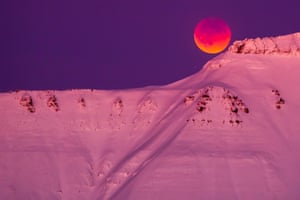 The moon peeps over the top of a mountain range in Longyearbyen, Svalbard, Norway
