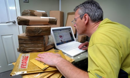 A seller trading on eBay with a pile of parcels.