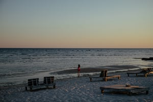 A young woman enjoys the sunset on the recently reopened beach at Biloxi, Mississippi.