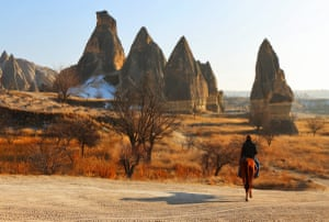 A lone rider, on horseback, amid the valleys and orange- and rust-coloured rock formations of Cappadocia in Turkey.