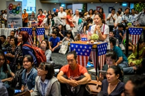 People watch live election results hosted by the US consulate general at a convention centre