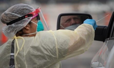 A healthcare worker prepares to use a swab to test a man for coronavirus in Houston, Texas, on 20 November.