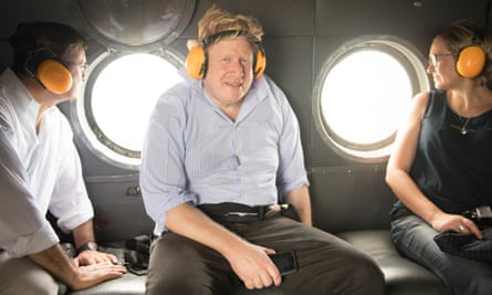 Johnson on board a helicopter with his Peruvian counterpart Nestor Popolizio (left) during a visit to the Amazon rainforest in May 2018.
