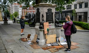 People looking at protest signs around the empty plinth where the statue of Edward Colston stood
