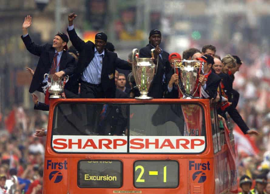Andy Cole keeps hold of the Champions League trophy as Manchester United parade their treble-winning silverware in 1999.