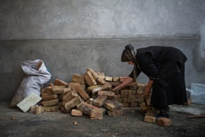 Kyrgyzstan's high level of unemployment and low income levels are the primary reasons for migration to Russia and Kazakhstan in search of work. <br><br>Mahfirat, a 60-year-old woman, collects bricks for the restoration of a destroyed house. Osh city, Osh oblast.