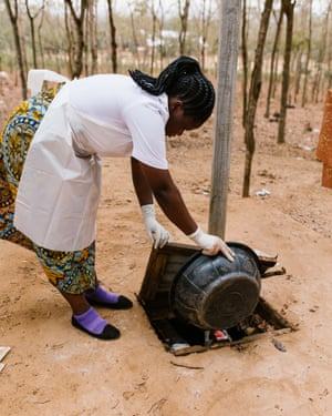 Nurse-midwife Jackeline Gideon Mwiguta carries the placenta and other waste out to the clinic's disposal pit - an unlined hole in the ground with a cover where medical waste is later burned