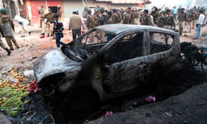 A burnt vehicle is pictured following clashes between supporters and opponents of a new citizenship law in New Delhi ahead of US president's arrival