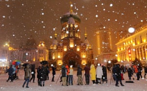 Harbin, China: People take photos of St Sophia Cathedral during the first snowfall in the region