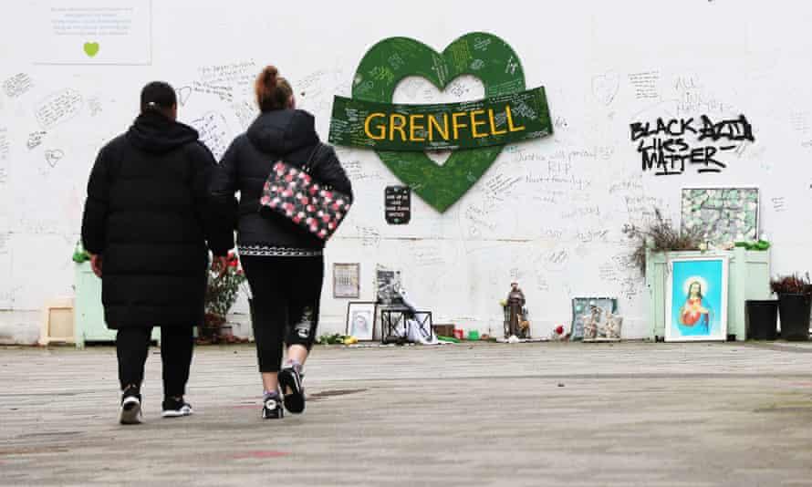 Two women walk towards the Grenfell Memorial Wall in the grounds of Kensington Aldridge Academy